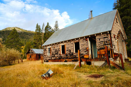 The decaying remains of an old abandoned home in the forest  located in the  California Sierra mountains  Imagens