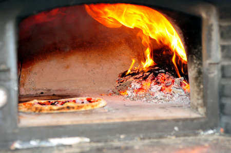Baking Pizzas in a wood burning pizza oven with glowing coals and embers with flames  shooting up Foto de archivo
