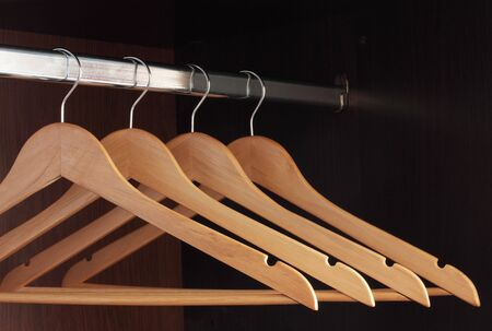 hangers: Wooden hangers hanging in an empty closet on the upper Stock Photo