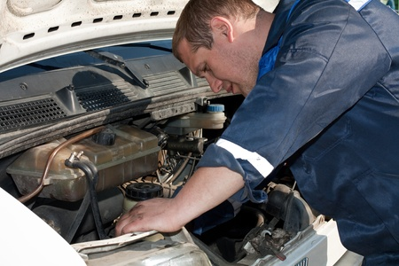 soot: man repairing a car with a raised soot