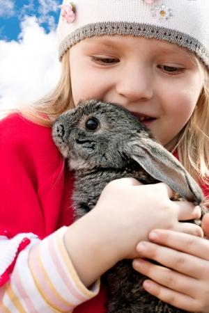 little girl holding a rabbit in her arms Stock Photo - 17362013