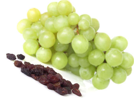 epicurean: Isolated yellow grape cluster and raisins on white background
