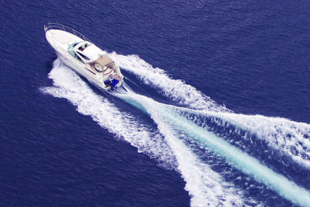 yacht race: fast motor boat with splash and wake