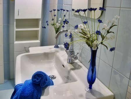 modern blue bathroom - detail on sink with towel and flowers