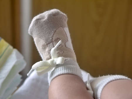 one childs foot in half-hose resembling shoes with shoelace Stock Photo