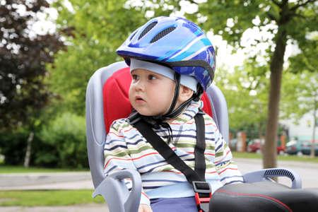 child sitting by bicycle in crash helmet Foto de archivo