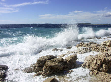Impact of large waves against rocks in the beach Stock Photo