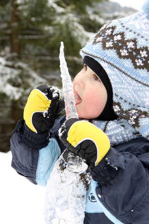 sopel lodu: Mały Chłopiec jeść Sopel w zimie na górach
