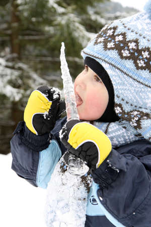 small boy eat icicle in winter on mountains