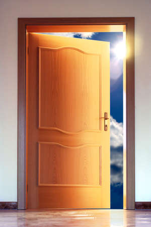 view of a wooden doorway: Opened door to blue sky with sun - conceptual image