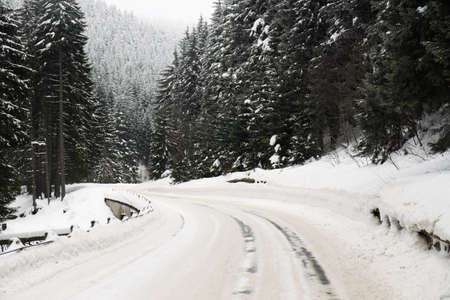 road curve in winter with lot of snow and snow barriers Stock Photo