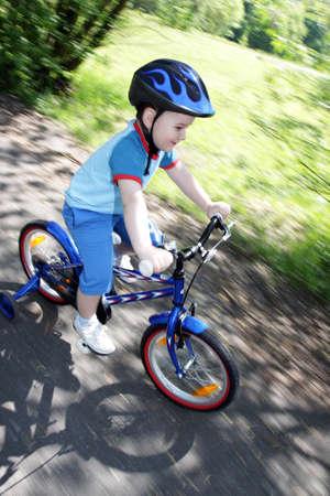 panning shot: joy game on child bicycle in spring in park - panning shot