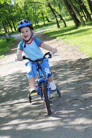 pedaling: joy game on child bicycle in spring in park Stock Photo