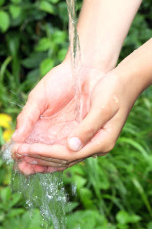 Child hand with clear water photo