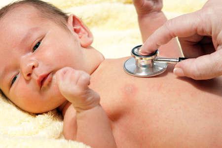 niños enfermos: Estetoscopio escuchando a un bebé Foto de archivo