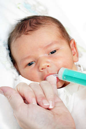 little boy drinking milk from the mother of the syringe photo