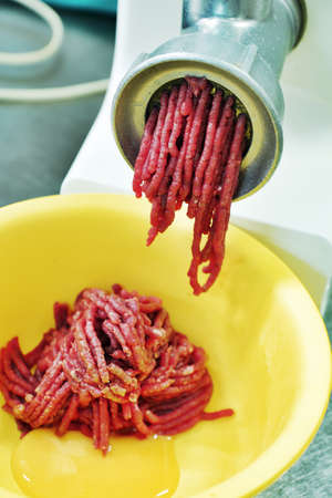 detail mincing machine in action in kitchen photo