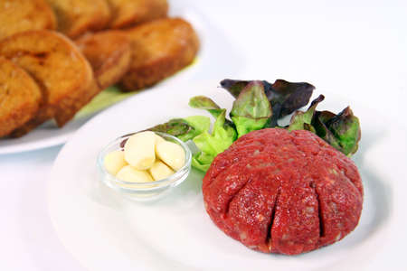 tartar: Steak tartare with garlic on white plate with onions and ketchup. Toast in background.