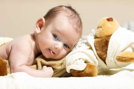 newborn lying on the cute toy bear photo