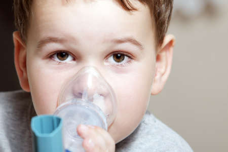 asthma: Close-up image little boy using inhaler for asthma. Stock Photo
