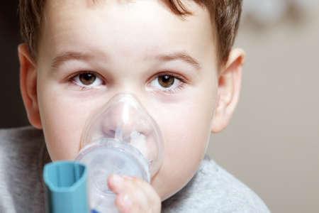 asthma: Close-up imagen de chico poco usando inhalador para el asma. Foto de archivo