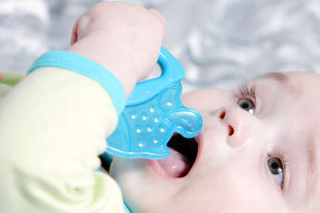 Cute baby with a blue fish teether Archivio Fotografico