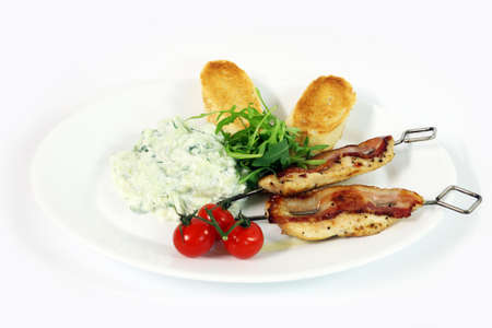 Greek food - tzatziki, chicken souvlaki with bacon and baguette on white background photo