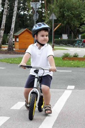 playground ride: Baby boy on traffic playground for childs with crash helmet