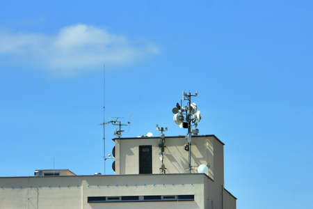 satellite communications dishes on roof panel building photo