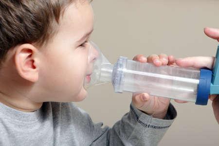 asma: Close-up imagen de chico poco usando inhalador para el asma. Foto de archivo