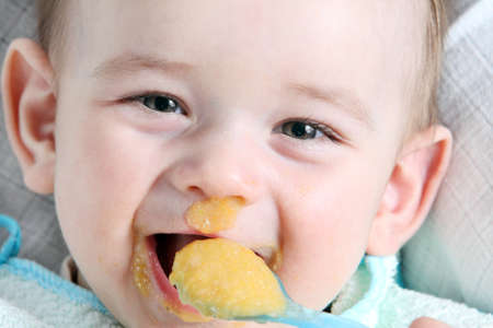 Laughter baby boy eating vegetable mash
