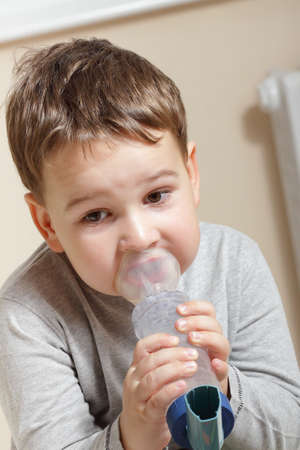 bronchitis: Close-up image little boy using inhaler for asthma. Stock Photo