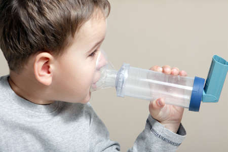 Close-up image little boy using inhaler for asthma. Archivio Fotografico