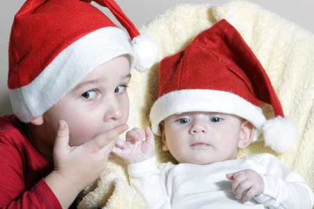 Beautiful child and newborn with Christmas hat photo