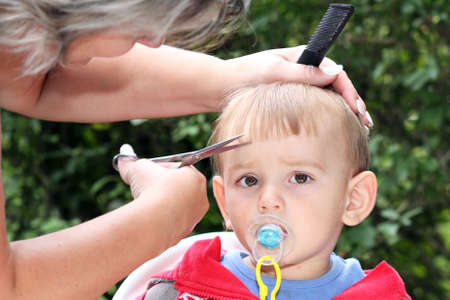 hair cutting first one-year-old child - trimming bangs Stock Photo