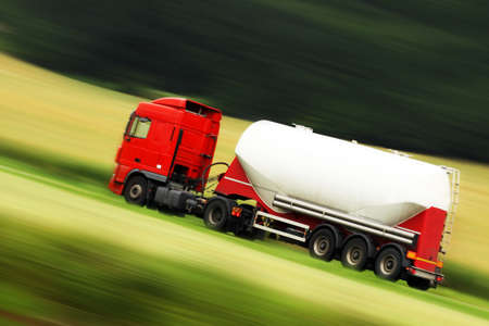 whitem: large white cistern truck speeding on highway with blurred countryside panorama in background