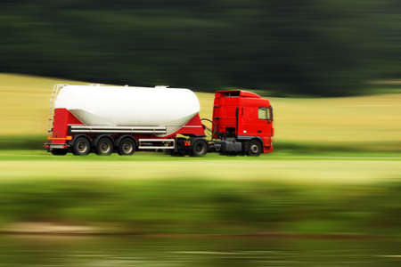 large white cistern truck speeding on highway with blurred countryside panorama in background photo
