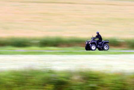 panning shot: Panning shot of a fast moving black ATV - quad bike