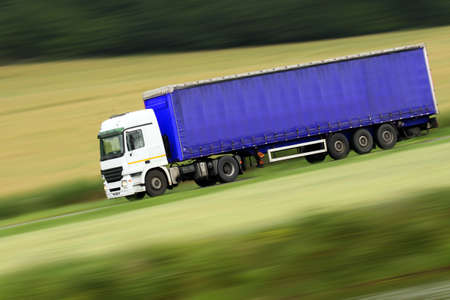 whitem: large blue truck speeding on highway with blurred countryside panorama in background