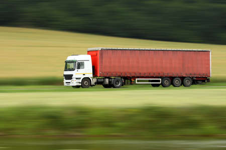 whitem: large red truck speeding on highway with blurred countryside panorama in background Stock Photo