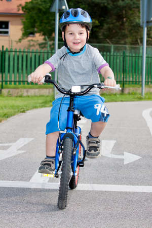 Baby boy on traffic playground for childs with crash helmet