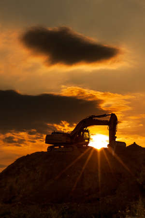 skyline excavator with colored sunset Stock Photo