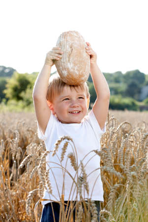 little boy with the bread over your head in the mature grain