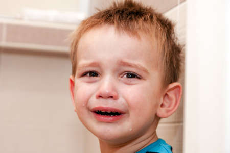 Portrait Of Crying Baby Boy In Home. photo