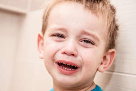 ojos tristes: Retrato de Crying Baby Boy In Home.