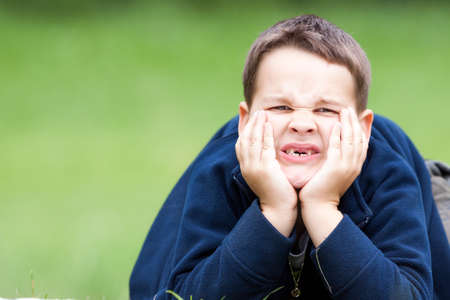 bad teeth: boy outdoors without upper two teeth with pain in the face Stock Photo