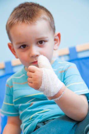 wounded in the left hand with bandage boy at shot in home photo