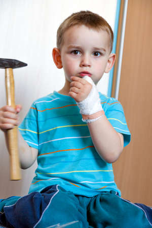 left hand: wounded in the left hand with bandage boy at shot in home