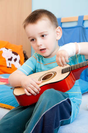 left hand: wounded in the left hand with bandage boy at shot in home with guitar Stock Photo