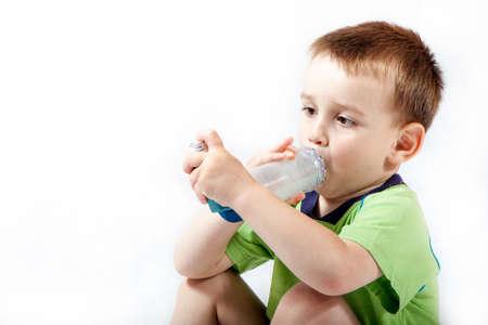 bronchitis: Little boy using inhaler for asthma isolated on white  Stock Photo